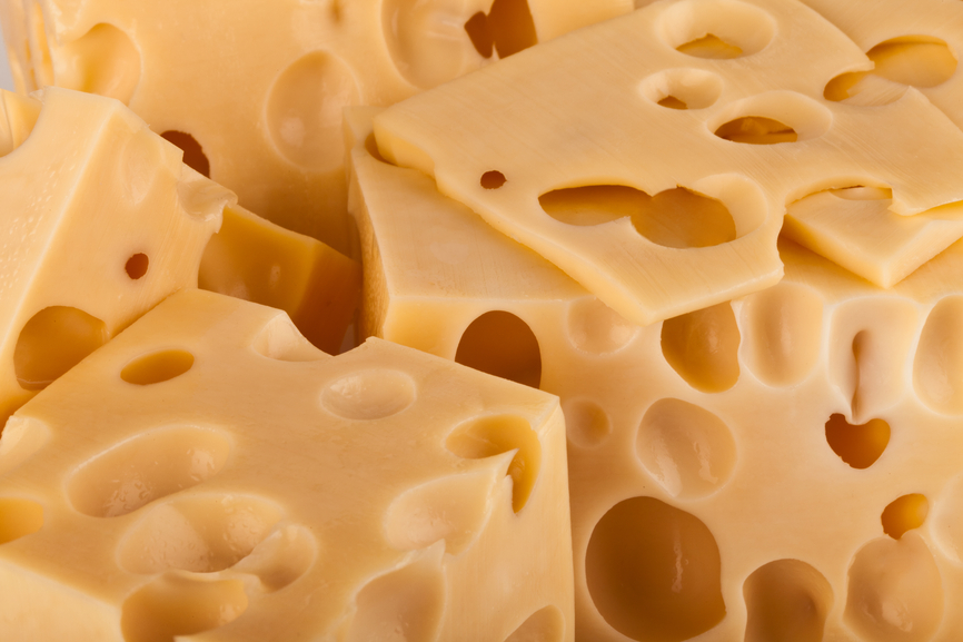 Background of fresh yellow Swiss cheese with holes